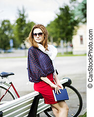 Woman rests on bench and hold book - Attractive woman rests...