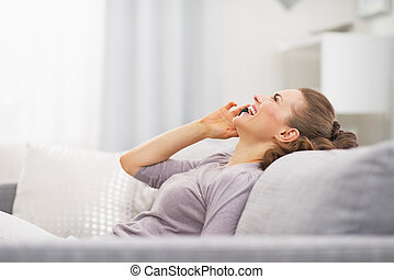 Happy young woman talking mobile phone while relaxing on...