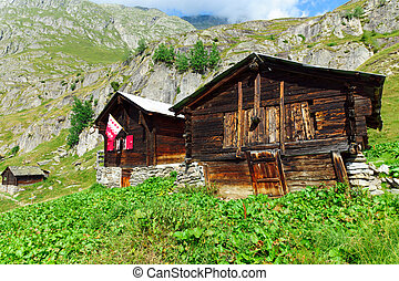 Two traditinal alpine huts seen in the swiss alps