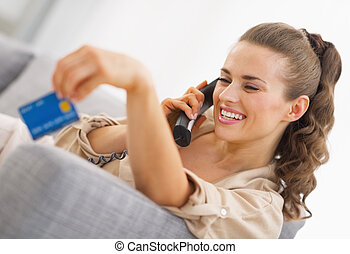 Happy young woman playing with credit card while talking...