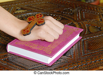 Religious life - Hand on red Bible with wooden cross