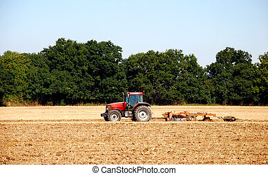 Tractor and harrow cultivating the soil - Red tractor and...