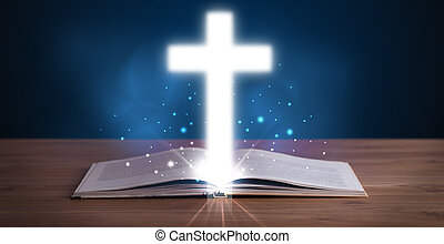 Open holy bible with glowing cross in the middle on wooden...