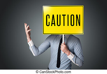 Businessman holding a caution sign - Businessman standing...