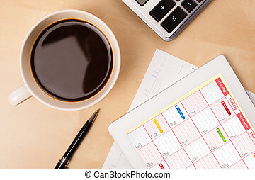 Workplace with tablet pc showing calendar and a cup of...