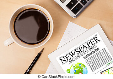 Tablet pc shows news on screen with a cup of coffee on a...