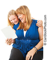 Mom Enjoys Greeting Card From Daughter - Mom laughs as she...