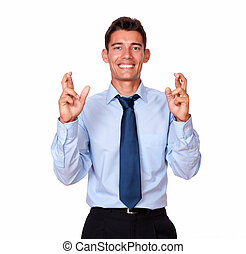 Charming hispanic businessman crossing his fingers
