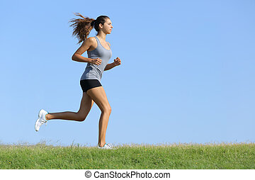 Beautiful woman running on the grass with the sky in the...
