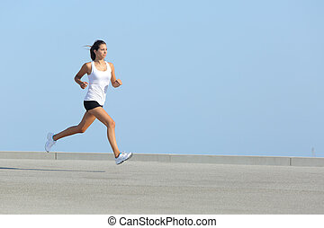 Beautiful woman running with the sky in the background -...