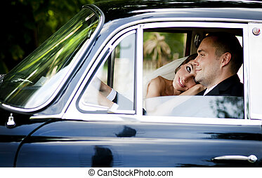 Bride and groom in car - Happy bride and groom in a black...