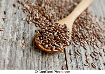 Flax seed - wooden spoon with flax seed placed on a wooden...