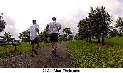 teammates running in park. sports