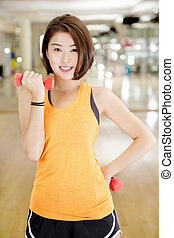 Weight lifting - An Asian lady doing weight lifting exercise...