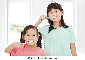 two happy little girls brushing her teeth