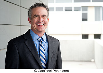 portrait of a confident mature businessman standing outside
