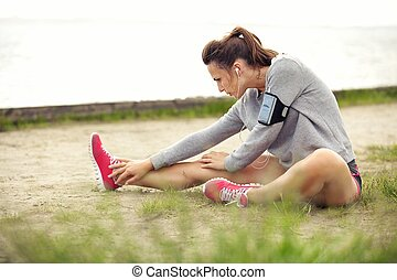 Woman Stretching Her Legs Before Workout - Woman in...