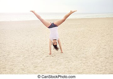 Cheerful Woman on the Beach Doing Handstand