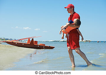 Lifeguard and rescued child - Lifeguard man with rescued...