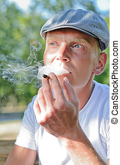 Man puffing on a home made cigarette that he has rolled from...