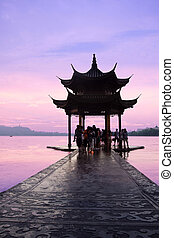 hangzhou,china - old pavilion silhouette adainst the sunset...