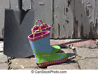 Childs wellington boots and shovel against an old brick wall