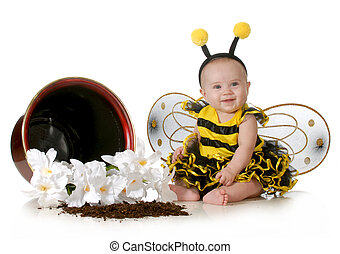 cute baby dressed up like a bumblebee sitting beside a...