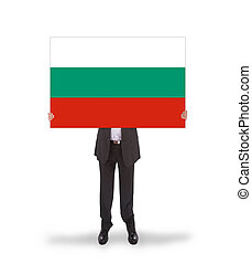 Smiling businessman holding a big card, flag of Bulgaria,...