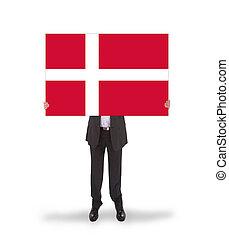 Smiling businessman holding a big card, flag of Denmark,...