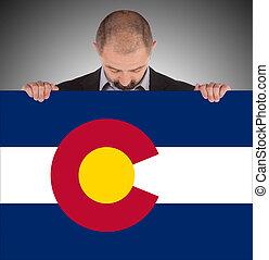 Smiling businessman holding a big card, flag of Colorado,...