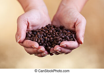 Handful of fresh roasted coffee on warm golden background