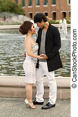 Young Couple embracing near the water fountain