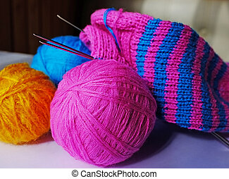 Knitting - Pink, blue and yellow woollen balls,...