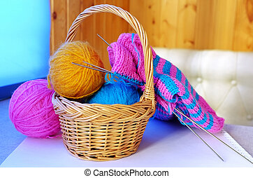 Knitting - Blue and yellow woollen balls in a small basket...