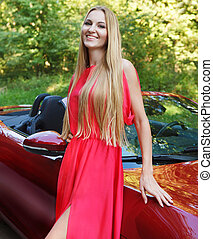 Beautiful blond young woman standing near a sports car -...