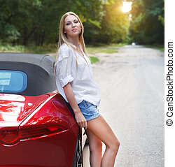Young woman standing near a sports car - Beautiful blond...