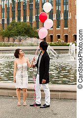 Vertical photo of young adult couple looking at several balloons overhead of them with water fountain, flowers, trees and brick building in background