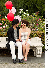 Vertical photo of young adult couple looking at each other while sitting down on a bench with several balloons, flowers and trees in the background