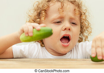 Happy little boy holding a  cucumber. Concept of healthy food.