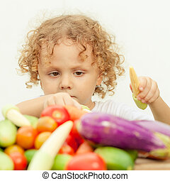 Happy little boy with vegetables . Concept of healthy food.