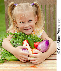 Happy little girl with vegetables . Concept of healthy food.