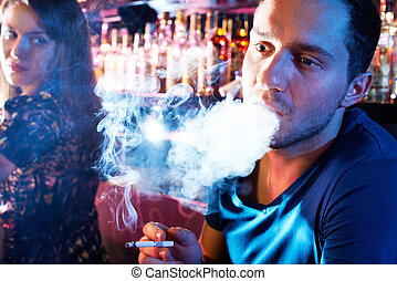 Guy smoking - Portrait of young man letting smoke out of...