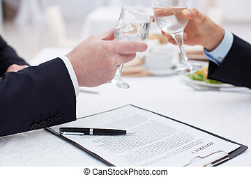 Drink success - Close up of business partners clinking...