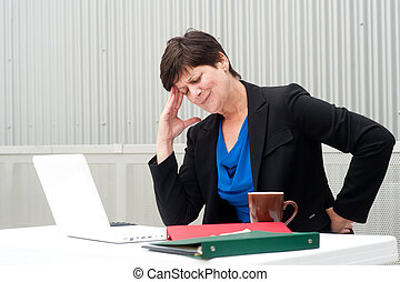 businesswoman under stress, fatigue, and headache at office