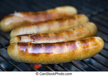 Sausages on charcoal grill - Sausages sizzling on a charcoal...