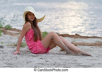 Cute young girl in hat sitting on the beach