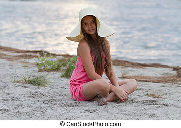 Cute little girl in hat sitting on the beach