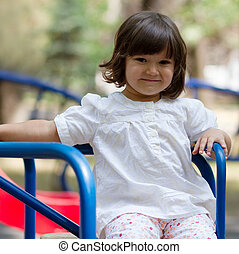 Little girl on a carousel in the park