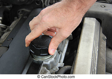Man checking the oil level of a car