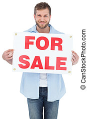 Charming young man holding a for sale sign